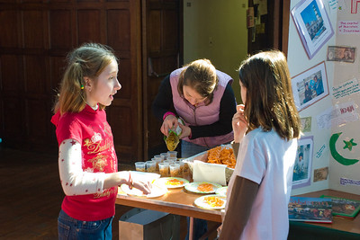 Kate putting out plates of jalebis, snack mix and mango lassi.