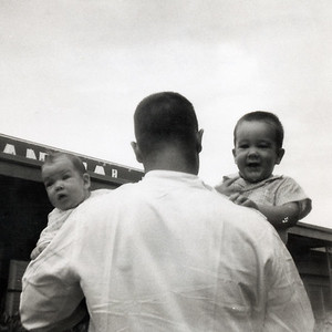 Daddy has two sweet babies. Grady Kane with John (14 months) and Kathy (2 months) in front of Grady's veterinary clinic at 1911 East Hwy 190, Killeen, Texas. July 1962.