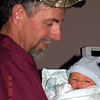 Kenny holds Michael. Peeping out of his blankie.