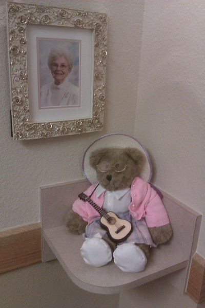 Decoration outside the door of Mom's apartment at Atria assisted living.  Bear was given to her on her 80th birthday, made to represent her with her guitar.