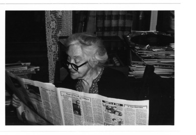 Grandma sitting in her dining room, reading the daily paper