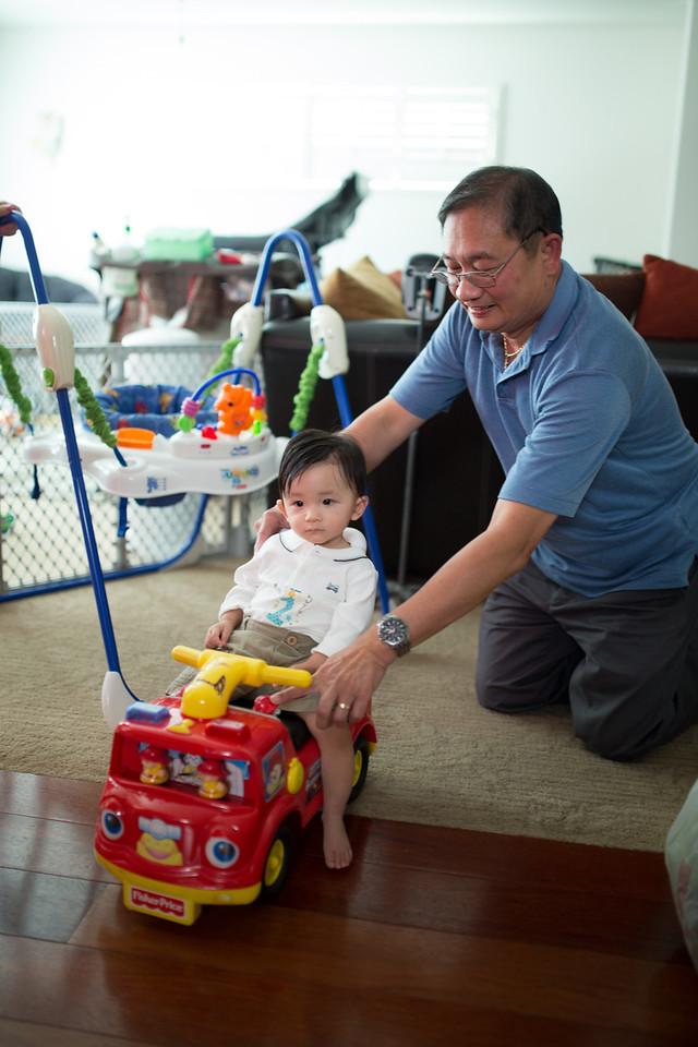 Grandpa Hai pushes Noah in his fire truck.
