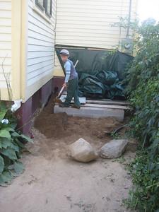 Liam helped spread the dirt around the new cinderblock bulkhead.
