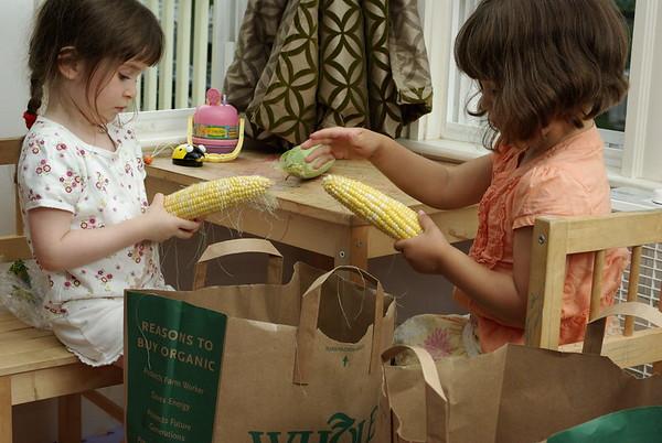 Shucking corn with Avani.
