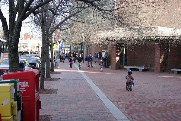 Guen and Atticus bike through Davis Square.