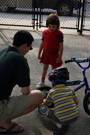 Guen watches Nikhil fix his bike.