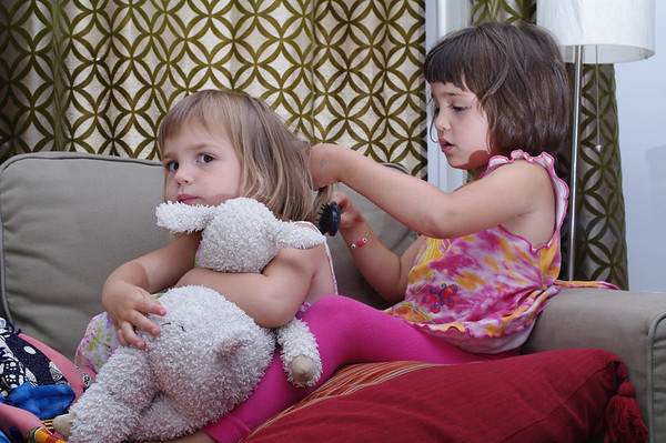 Anya squeezes the sheep so the tangles don't hurt.