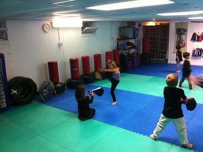 Guen helps Anya practice her kicks.