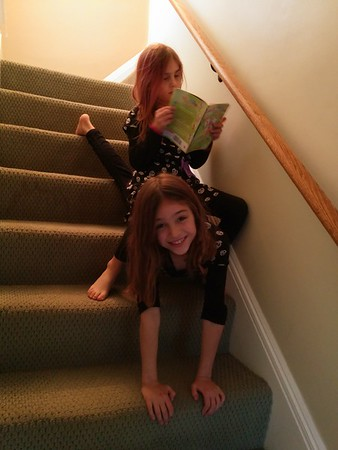 Guen is helping Anya down the stairs so Anya can continue reading.