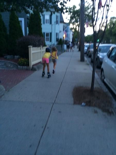 Anya pulls Guen on rollerblades.