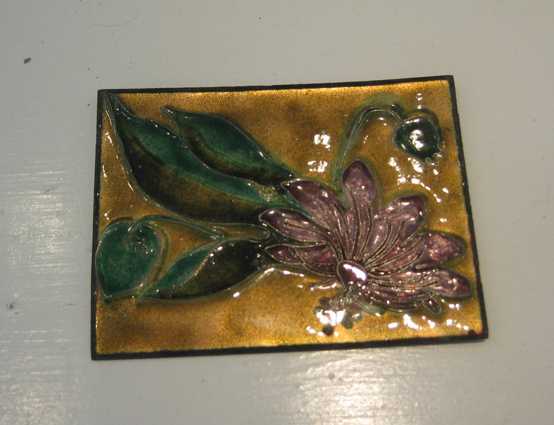 Copper as a base with fine metal partitions rendered by hand and then colored glass poured, this one measures about 6 inches square.