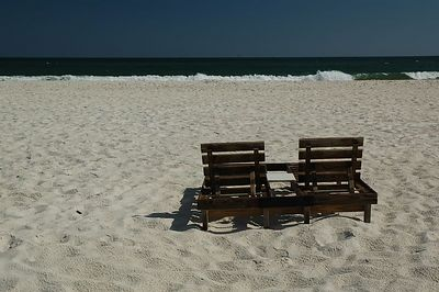 Chairs, sand, surf, sky.