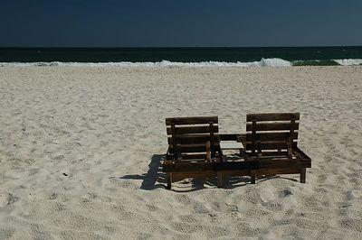 Chairs, sand, surf, sky.
