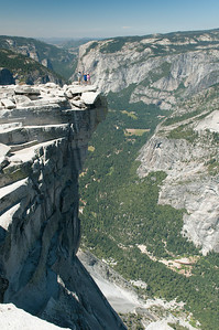 """Kevin, Sara and Steph on the """"Diving Board"""" a rocky ledge at the top of Half Dome - Yosemite Valley down below"""