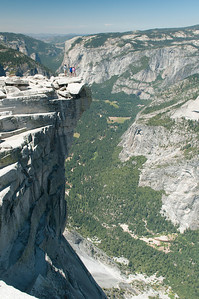 "Kevin, Sara and Steph on the ""Diving Board"" a rocky ledge at the top of Half Dome - Yosemite Valley down below"