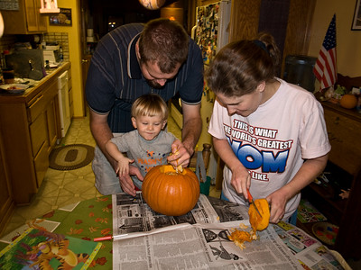 Mom scrapes off the top of the pumpkin while dada and Cody pull some seeds out.