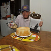 Tex displaying birthday presents -- cherry pie, angel food cake, and a book about ranching.