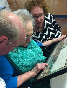 After the graveside service, we gathered at the Christian Church, Barnsdall, OK and enjoyed family conversations in the air-conditioned Fellowship Hall.  Rae and her two oldest children, JohnR and Lillian, examined an old photo, trying to identify faces...
