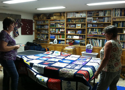 Deb (right) showed Bev a T-shirt quilt that she has made.   Before and after this photo, the ping-pong table was in active use.