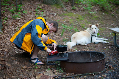 At the campsite, Rich tries to get the stove going to heat up water.