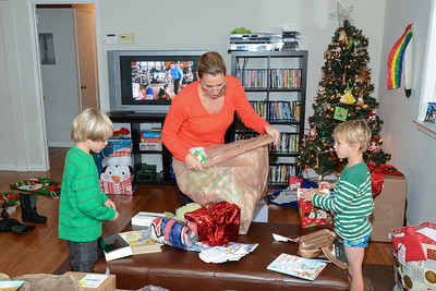 Mom cleans up as the boys unwrap presents.