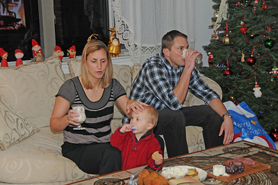 Saxon tries some chap stick while mom and dad try the eggnog.