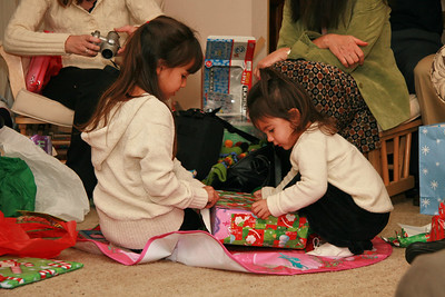 Alexa and Annika open a gift together.