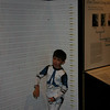 An exhibit demonstrating the similarity in Chimp and Human DNA.  The places where humans are different are marked with a little person.  Can you find any?  There is one right above Ryan's right elbow.
