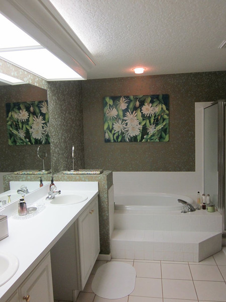 """Master bathroom. The previous owner had a """"thing"""" for busy, dark colored wallpaper.  Eventually, this room will be updated with a more contemporary paint color and new countertops/sinks."""