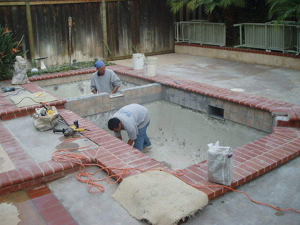 Tile in place in the pool the guys work on finishing up before the plaster.