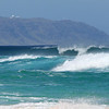 Surf at Banzai Pipeline with Kaena Point in Background
