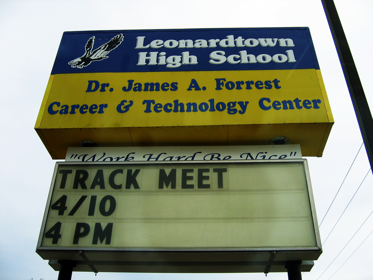 The school sign just outside the parking lot.  The lot was overcrowded with cars.