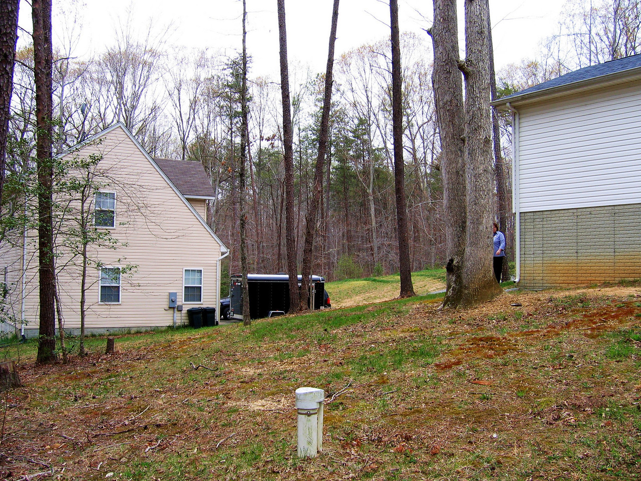 A view of the neighbor's house and the septic access tube in the foreground.
