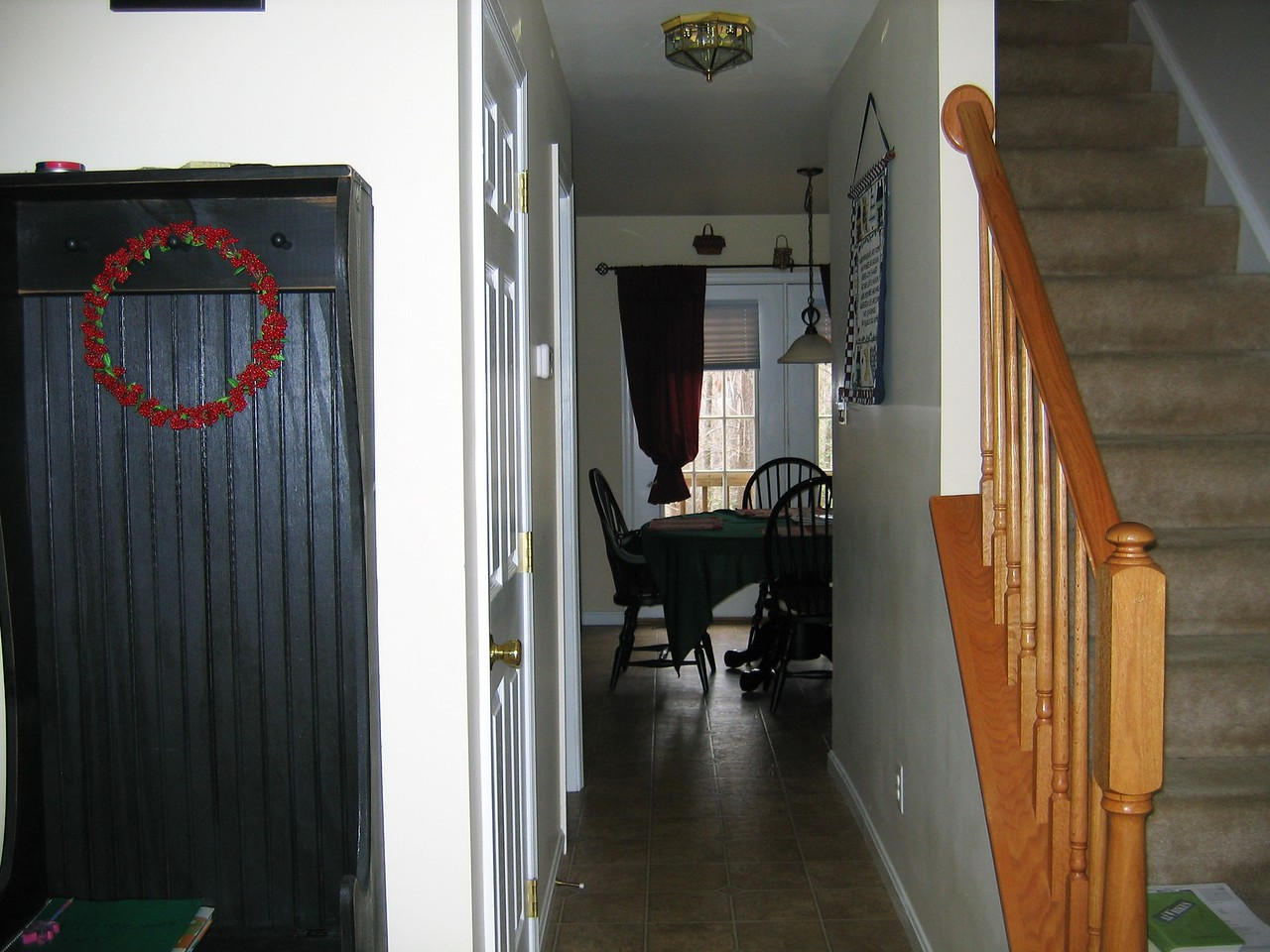 View from the entryway looking back towards the dining area and stairs to the second level are on the right.  The floors are linoleum and the carpet is a neutral beige shag carpet.