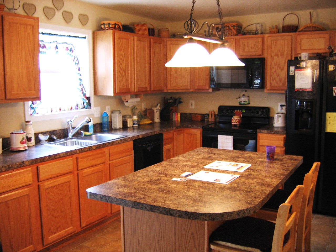 The kitchen has an island with formica countertops and oak trim cabinets.  The appliances are new and the stove is a hot point style.