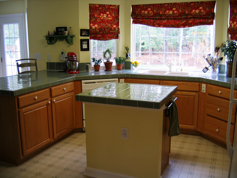 The kitchen has an island and upgraded green ceramic countertops (Missy would love the colors) and oak cabinets.