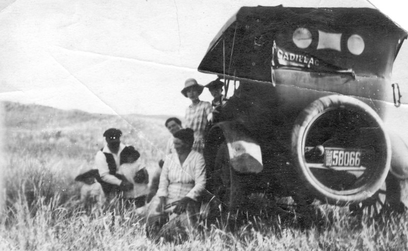 "1920 - Dorothy Hutchinson in checkered dress & hat. I believe the word ""Cadillac"" on the vehicle refers to where the Hutchinson family lived in 1920 - Cadillac, Saskatchewan, rather than the model of the vehicle  ;-)"