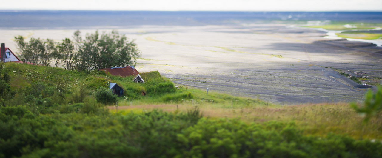 Grass roof farmhouse in Skaftafell overlooking glacier wash out (tilt shift)