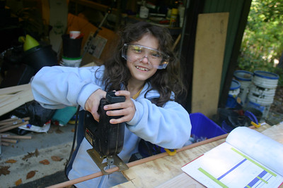 Anisa helping cut the dowels for her loft bed.  She got pretty good at using the scroll saw and the power drill.