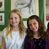 Anisa and Annie outside the theater with Shipley artwork on the wall behind them.