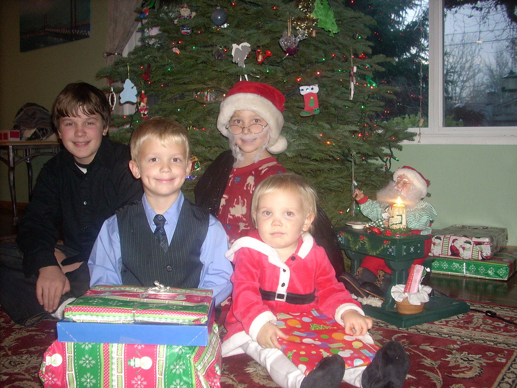 Christmas card photo.  Annora kept taking Elliot's present and he was mad but still smiled for the photo.  Chris 13, Ian 8, Elliot 5, and Annora is 19 months old.