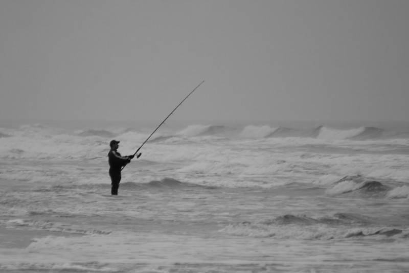 A black and white of a fisherman in the surf.