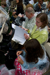 Everyone keeping busy while the names are being read out.  Since every single senior and graduate student gets their degree in person, about 2000 people, it takes a while.  Anisa working on an art project, Linda doing her work, her dad doing a NYT crossword puzzle and Christine reading.