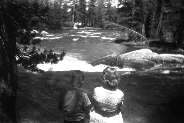 Marc and Ruth McChesney at Tolumune Meadows, Yosemite in July, 1956.  They are standing on the bridge over the Tolumune River, which was flowing at a very fast pace.  Lots of snow!.  At that time the road was mostly one lane between Tioga Pass and the Valley.