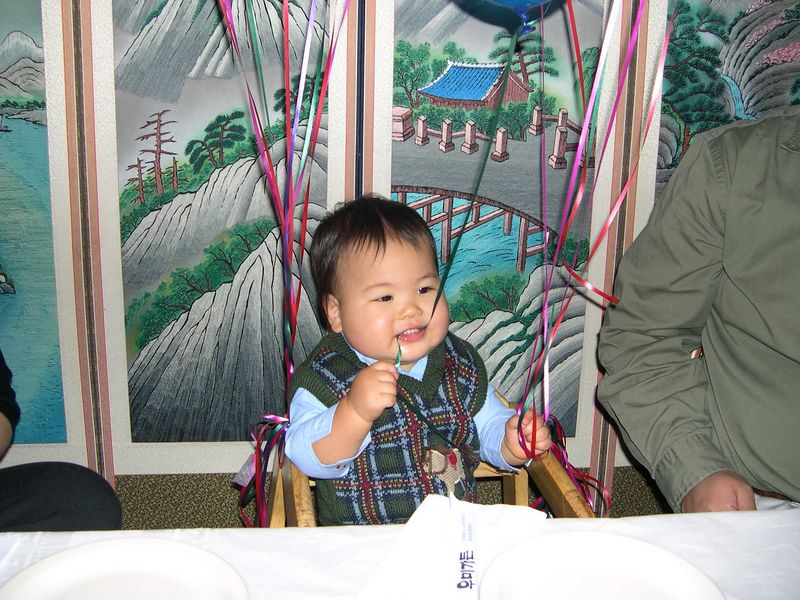 Jonathan chews on a balloon string.