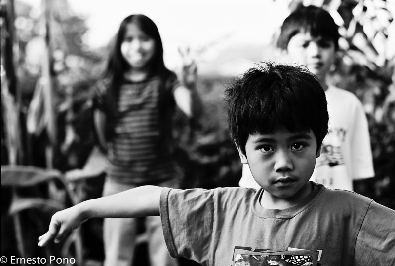 I don't know why, but this is one of my favorite pictures of the kids.  For some reason, Josh lifted his arms and gave me that serious look.  Jaz was giving the Peace sign, and Jared looks uninterested.<br /> <br /> This was taken in my dad's backyard in Vallejo.  My dad's backyard has tons of vegetable plants in it (tomatoes, beans, eggplant, etc).  He spends many hours out there tending to them.  When the kids were younger, they spent time with my dad out there climbing through plants and petting the stray cat (Sheba) who hung around.<br /> <br /> Sheba wasn't officially my dad's cat, but he fed it when she came around.  That cat was hanging around for >8 years.  A couple of years ago, sadly, she was hit be a car and died.<br /> <br /> Camera geek info:  This was back in my film days.  Probably taken with the Contax Aria and 50 mm Zeiss lens.  I really love that lens.