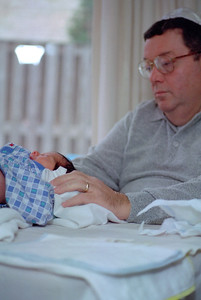 Jerry Berenzweig in role as 'sondek' during the bris of his first grandchild, Joshua Beremzweig. Rockville, MD  November, 1997  Pentax ME Super with 80-200mm lens (probably), Vivitar 285 flash with Lumiquest 80-20 flash reflector (seen in window) Scanned with Minolta Scan Dual II in August 2016.