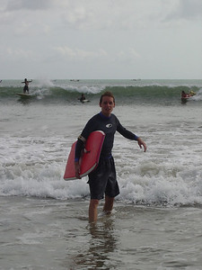 surfing the waves at Kuta Beach, in Bali, Indonesia