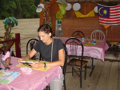 reading Colin's diary entry for the day while waiting for supper on our floating restaurant, Taman Negara.