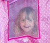 Big sister Maddie peeks out through the tent window.